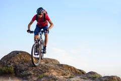 Велосипедист в красном цвете ехать велосипед вниз с утеса на предпосылке голубого неба Весьма спорт и концепция Enduro велосипед Стоковые Изображения