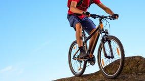 Велосипедист в красном цвете ехать велосипед вниз с утеса на предпосылке голубого неба Весьма спорт и концепция Enduro велосипед Стоковое Изображение