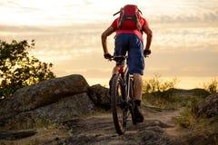 Велосипедист в красном цвете ехать велосипед на скалистом следе на заходе солнца Весьма спорт и концепция Enduro велосипед Стоковые Фото