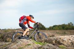 Велосипедист в красном цвете ехать велосипед на скалистом следе на заходе солнца Весьма спорт и концепция Enduro велосипед Стоковые Изображения RF