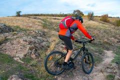 Велосипедист в красном цвете ехать велосипед на следе осени скалистом Весьма спорт и концепция Enduro велосипед Стоковые Фото
