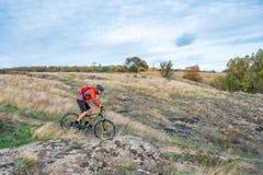 Велосипедист в красном цвете ехать велосипед на следе осени скалистом Весьма спорт и концепция Enduro велосипед Стоковое Изображение RF