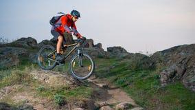 Велосипедист в красном цвете ехать велосипед на следе осени скалистом на заходе солнца Весьма спорт и концепция Enduro велосипед Стоковое Изображение