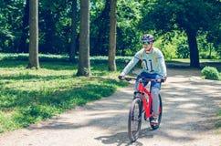 Велосипедист в шлеме на оранжевом катании велосипеда в парке Стоковая Фотография