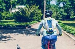Велосипедист в шлеме на оранжевом катании велосипеда в парке Стоковые Фото