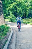 Велосипедист в шлеме на оранжевом катании велосипеда в парке Стоковые Фотографии RF