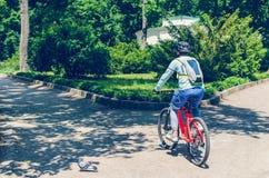 Велосипедист в шлеме на оранжевом катании велосипеда в парке Стоковые Изображения