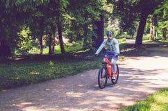 Велосипедист в шлеме на оранжевом катании велосипеда в парке Стоковое Изображение