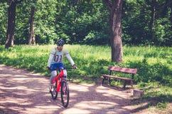 Велосипедист в шлеме на оранжевом катании велосипеда в парке Стоковое Фото