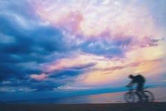 Велосипедист горы на пляже и заходе солнца небо бурное Стоковые Изображения
