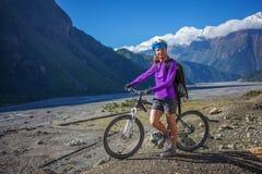 Велосипедист-девушка в горах Гималаев, зона Anapurna Стоковое Изображение RF