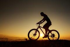 Велосипедист-девушка на заходе солнца на горах Стоковые Изображения