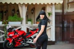 Велосипедист девушки в черных одеждах на мотоцикле спорт представляя в городе Стоковая Фотография RF