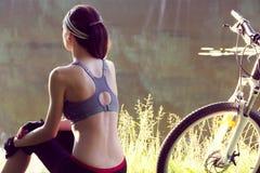 Велосипедист девушки около реки Стоковые Изображения RF