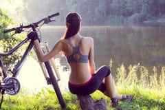 Велосипедист девушки около реки Стоковая Фотография