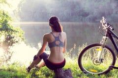 Велосипедист девушки около реки Стоковое Изображение