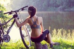 Велосипедист девушки около реки Стоковое Фото