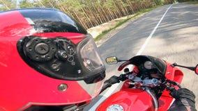 Велосипедист едет красный мотоцикл на дороге, нося шлем сток-видео