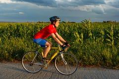 Велосипедист едет на велосипеде дороги вдоль поля В предпосылке красивое голубое небо Стоковые Фото
