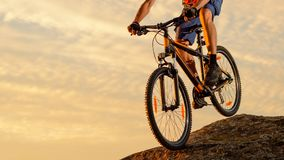 Велосипедист ехать велосипед вниз с утеса на заходе солнца Весьма спорт и концепция Enduro велосипед стоковые фото