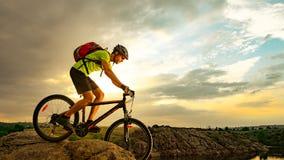 Велосипедист ехать велосипед на скалистом следе на заходе солнца Весьма спорт и концепция Enduro велосипед стоковая фотография