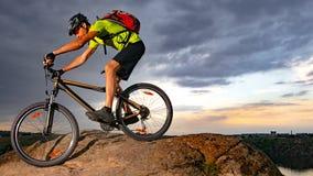 Велосипедист ехать велосипед на скалистом следе на заходе солнца Весьма спорт и концепция Enduro велосипед стоковая фотография rf