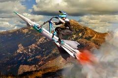 Велосипедист, летая вверх вверх на ракету Стоковая Фотография