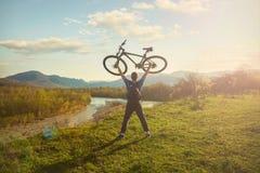 Велосипедист мальчика стоя на горе и взглядах на реке на велосипедисте захода солнца a держит велосипед над его головой Стоковые Фотографии RF