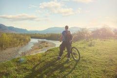 Велосипедист мальчика стоя на горе и взглядах на реке на концепции захода солнца для путешественников Взгляд от задней части тури Стоковое Фото
