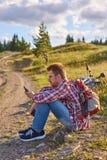 Велосипедист молодого человека сидит на краю грязной улицы стоковые фото