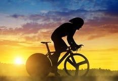 Велосипедист на велосипеде гонок дороги на заходе солнца Стоковые Изображения