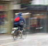 Велосипедист на проезжей части города на дождливый день стоковое изображение rf