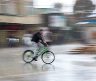 Велосипедист на проезжей части города на дождливый день стоковые фотографии rf