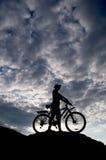 велосипедист пасмурный напротив неба силуэта Стоковое Фото