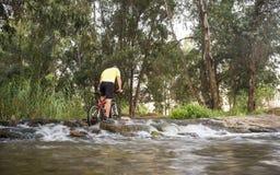 Велосипедист пересекая отмелый пропуск на низменности реки гвадианы, Sp реки Стоковые Изображения RF