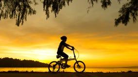 Велосипедист силуэта на заходе солнца Стоковое Изображение RF