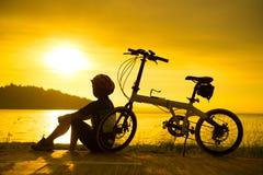 Велосипедист силуэта на заходе солнца Стоковые Фото