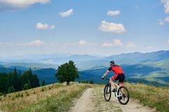 Велосипедист спортсмена в по пересеченной местностях sportswear и катания шлема bicycle на дороге горы Стоковые Фото