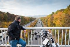 Велосипедист с взглядами мотоцикла на шоссе стоковая фотография rf