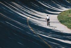 Велосипедист с горным велосипедом вдоль пути в старой беговой дорожке, скоростной дороге параболистической в Autodrome Монцы - Ло стоковая фотография rf