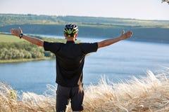 Велосипедист с рюкзаком на его перемещении горного велосипеда на береге Путешественник имеет adventur на луге на береге реки Стоковая Фотография RF