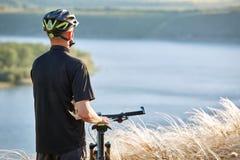 Велосипедист с рюкзаком на его перемещении горного велосипеда на береге Путешественник имеет adventur на луге на береге реки Стоковые Изображения