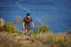 Велосипедист с рюкзаком на его перемещении горного велосипеда на береге Путешественник имеет adventur на луге на береге реки Стоковое фото RF