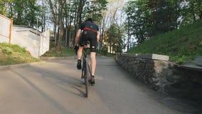 Велосипедист с сильными ногами pedaling из седловины взбираясь холм Задействуя концепция тренировки Следовать съемкой ( сток-видео