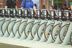 Велосипеды на специализированной автостоянке на улицах с возможностью для того чтобы арендовать велосипед стоковое изображение