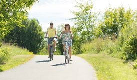 Велосипеды счастливых молодых пар ехать летом стоковые фотографии rf