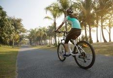 велосипед катания велосипедиста женщины в тропическом парке весны Стоковые Фотографии RF