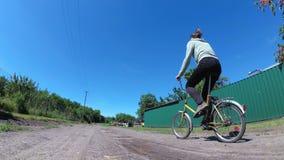 Велосипед катания молодой женщины винтажный вдоль сельской дороги в деревне сток-видео