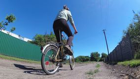 Велосипед катания молодой женщины винтажный вдоль сельской дороги в деревне видеоматериал