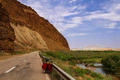 Велосипед, который нужно путешествовать в дороге Ирана с долиной и зеленой травой на стороне Оранжевые утесы и горы пустыни стоковое изображение
